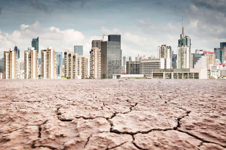 climate change: A city looks over a cracked earth landscape Stock Photo