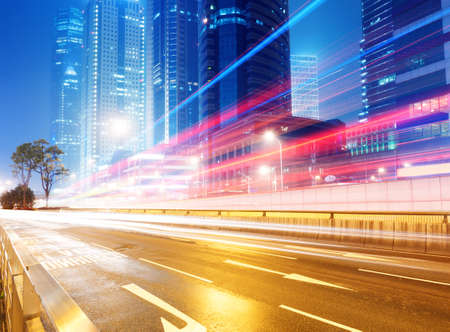 red traffic light: the light trails on the modern building background in shanghai china. Stock Photo