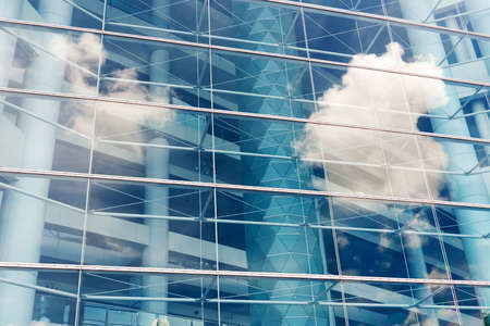exterior architecture: Clouds reflected in windows of modern office building Editorial