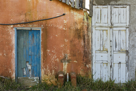old blue and white wooden doors of an abandoned orange house - horizontal