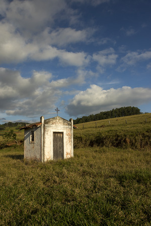 small white chapel on a pasture in the countryside of sao paulo - wide angle vertical Stock Photo