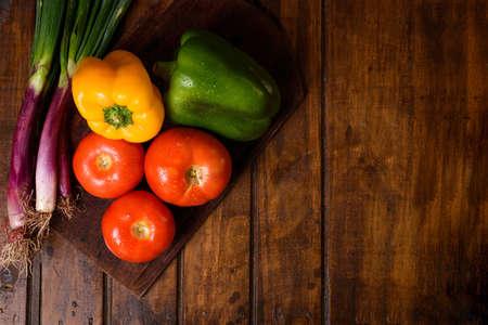 Ecological harvest of vegetables. Vegetarian ingredients for cooking on dark rustic wooden background, top view