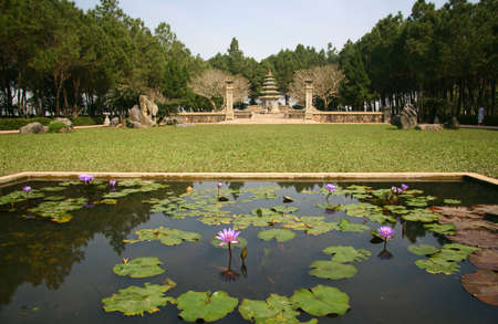 prayer tower: Temple in Hanoi, Vietnam, with a pond in the foreground with flowers Stock Photo