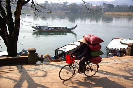 hue: Women carrying bags Vietnamese cycling in Hue, Vietnam, next to the 7-storey pagoda