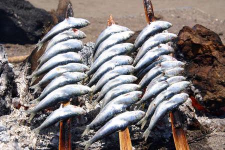sardinas: Las sardinas en una brocheta de le�a en la playa Foto de archivo