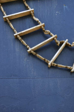 backstairs: wooden ladder on the wall of a blue boat Stock Photo