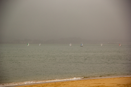 Sail boat race in the fog seing from the beach