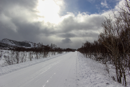 Snow white road to the lodge with the sun coming out between the clouds Stock Photo