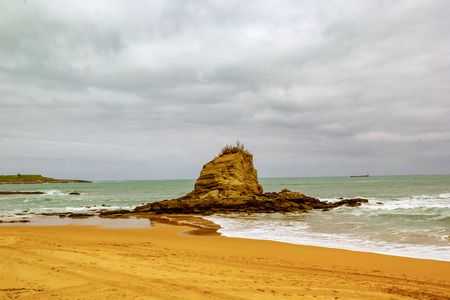 Rock in the middle ofthe beach with warm tones and a cloudy sky