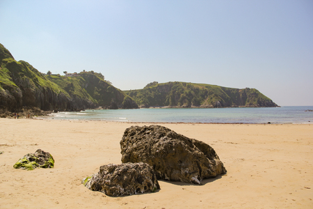 Stones on the beach as foreground to beautiful green cliffs