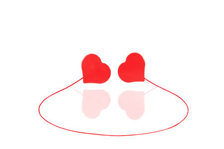 Twee rode harten bevestigd door een rode lijn met een spiegel reflectie geïsoleerd op wilgeteen
