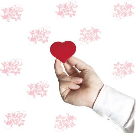 Mano che offre un piccolo cuore rosso in un muro bianco con fiori rossi
