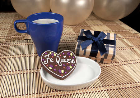 Sweet cooky with spanish love text  Te quiero , gift box, cup of coffee and balloons