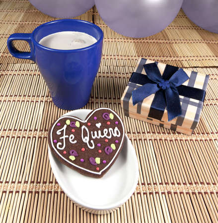 Sweet cooky with spanish love text  Te quiero , gift box, cup of coffee and balloons   photo