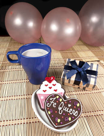 cooky: Sweet cooky with spanish love text  Te quiero  other cup cake cooky, gift box, cup of coffee and balloons   Stock Photo