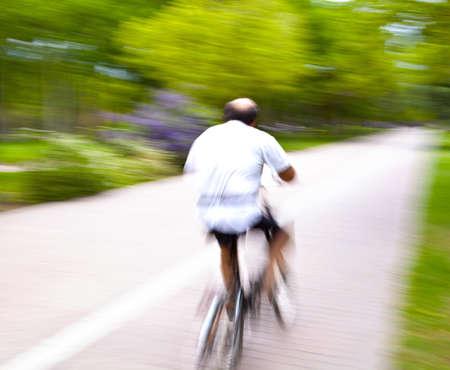 Equitazione bicicletta sulla luce del mattino attraverso il parco