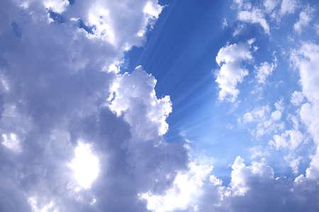Sfondo blu cielo nuvoloso con razzi sole