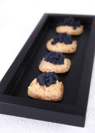 Caviar and salmon canape in wood tray