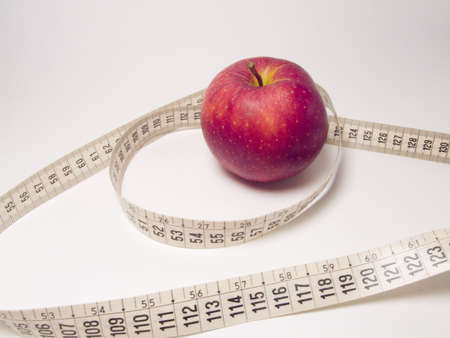 A red apple with a meter to represent diet and lost of weight photo