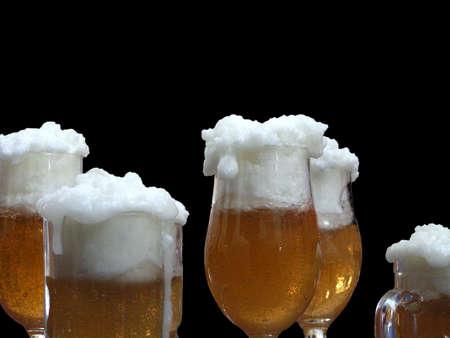 Blonde beer glasses against a black background