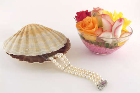 A pearls bracelet going out from a shell and flowers as decoration Stock Photo - 799750