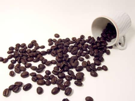 going out: Chicchi di caff� di uscire da una tazza su uno sfondo bianco Archivio Fotografico