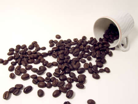 going out: Coffee beans going out from a cup on a white background Stock Photo