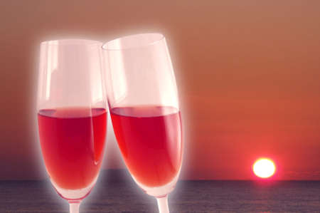 Two glasses with red wine while the sun is going down photo
