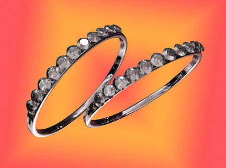 Two rings with diamonds against a colorful background photo