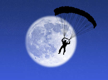 Parachutist in silhouette against a brilliant moon Stock Photo
