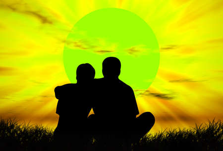 Lovers on the grass in front of the sunset photo