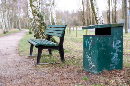 A green park bench with garbage can in the park in the middle between birch trees