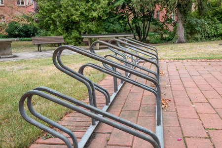 Berlin, Berlin/Germany - 19.07.2019: A metal bicycle stand for several bicycles on a path in front of a lawn with parking spaces of different heights.