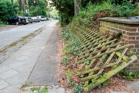 Berlin, Berlin/Germany - 06.08.2019: A collapsed wooden garden fence, lying on its side and already grown in by plants. Stock Photo