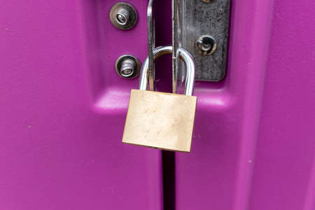 A padlock that closes and locks a pink coloured sliding door.