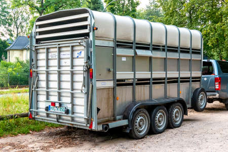 Berlin, Berlin/Germany - 06.08.2019: A horse trailer with three axles from behind with loading ramp and reflector