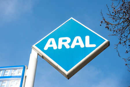 Berlin, BerlinGermany - 24.03.2019: The logo and lettering of an Aral petrol station photographed against the blue sky, at the corner of the picture the price board can be seen a little bit.
