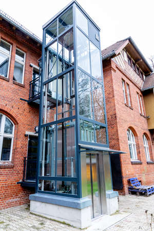 Berlin, Berlin/Germany - 24.03.2019: An outdoor elevator on a brick facade for unhindered access to all floors for the disabled.