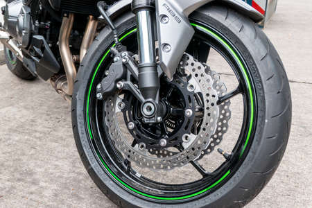 Berlin, Berlin / Germany - 07/16/2019: A motorcycle front tire with disc brakes parked on a street.
