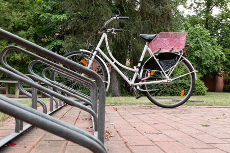 Berlin, BerlinGermany - 16.07.2019: A bicycle rack made of galvanized metal with a parked bicycle and pink shopping basket
