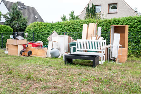 Berlin, Berlin/Germany - 30.07.2019: Bulky waste that has been placed in front of a plot of land and is waiting for removal by the local waste disposal company, including metal, wood and home furnishings.