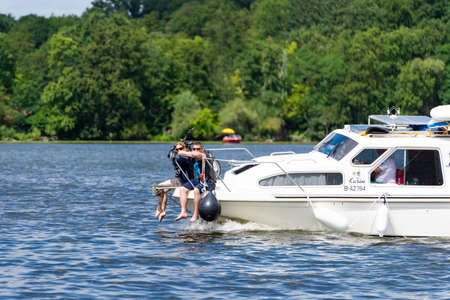 Potsdam, Brandenburg/Germany - 07.23.2018: Two persons who have their legs hanging over the railing on the bow of a motorboat and are therefore exposed to a high risk of an accident.