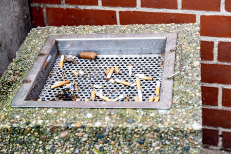 Berlin, BerlinGermany - 24.03.2019: Ashtray made of stone in front of a red brick wall with many cigarette butts and a cigar butt, which have already got wet from the rain.