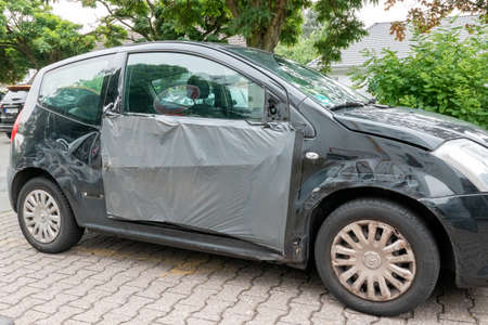 Berlin, Berlin / Germany - 30.07.2019: An accident-damaged black Citrön, who is poorly taped with a foil and continues to drive on the public road traffic hazard.