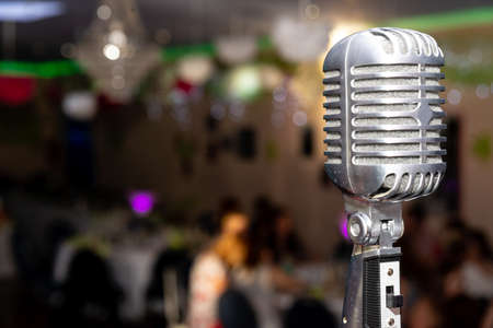 An old microphone standing on a stage in front of a decorated ballroom. The microphone has a switch and is nostalgic.