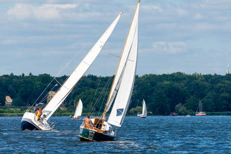 Berlin, Berlin/Germany - 07.23.2018: Two sailboats which lie in the wind on the Wannsee in Berlin and at the same time make a U-turn.