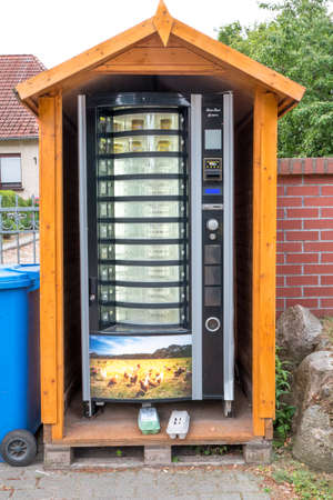 Berlin, Berlin/Germany - 19.07.2019: A vending machine at a farm where eggs and honey are sold. It is protected by a small wooden hut.