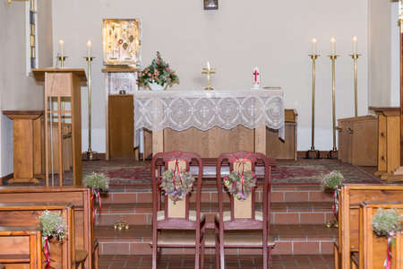 Berlin, Berlin/Germany - November 3, 2018: Interior and altar in the interior of a church with two chairs in the aisle for bridal couple of a wedding. Decorated with flowers and candles. Editoriali