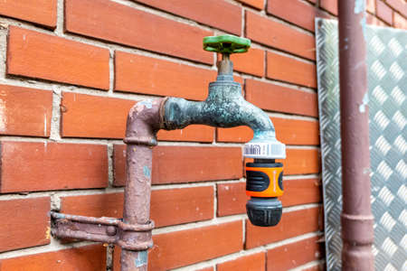 Berlin, Berlin/Germany - 11.07.2019: An old water tap covered with verdigris on a clinkered house wall with Gardena hose connection without hose
