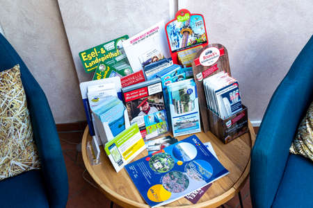 Berlin, Berlin/Germany - 03.09.2019: A table and armchair on which brochures for tourist destinations and offers are spread out or offered in brochure stands. Redakční